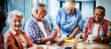 Healthcare worker serving coffee to senior people stock photography