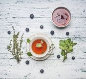 Healthful autumn hot herbal tea with berries, thyme and mint, jam from a rose, a spoon, a cut lemon, on a rustic wooden background. Healthful autumn hot herbal stock photos