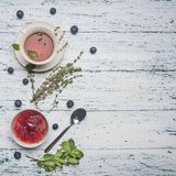 Healthful autumn hot herbal tea with berries, thyme and mint, jam from a rose, a spoon, cut lemon, on a rustic wooden background. Healthful autumn hot herbal tea stock images