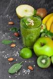 Healthful frukter och ett exponeringsglas av coctailen från kiwin på ett mörker - grå stenbakgrund Saftiga ingredienser för strik arkivbilder