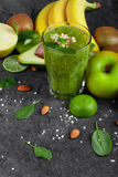 Healthful frukter och ett exponeringsglas av coctailen från kiwin på ett mörker - grå stenbakgrund Saftiga ingredienser för strik fotografering för bildbyråer