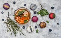 Healthful hot herbal tea with berries, thyme and mint, appetizing, multicolored macaroons on white rustic background, top view imagem de stock royalty free