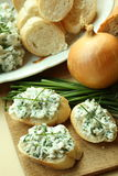 Healthly snack. Baguette slices with spread from chives on cutting board Royalty Free Stock Photos