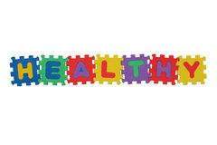 HEALTHY. Word HEALTHY, from letter puzzle, isolated on white background Stock Images