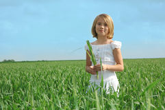 Healthy. A girl standing in a field of green against a blue sky. A child in a white dress smiling holding some leaves in her hands Stock Photo