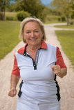 Healthy active elderly woman out jogging. On a country road approaching the camera with a happy smile in a health and fitness concept stock images