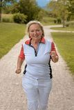Healthy active elderly woman out jogging. On a country road approaching the camera with a happy smile in a health and fitness concept stock image