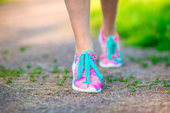 Healthy active lifestyle woman athlete tying running shoes. Sporty girl getting ready for jogging workout. Closeup of Stock Photos