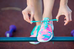Healthy active lifestyle woman athlete tying running shoes. Sporty girl getting ready for jogging workout. Closeup of Royalty Free Stock Photography