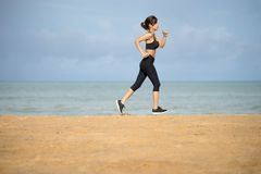 Healthy active lifestyle. Young sports fitness woman running on the beach at sunset royalty free stock photography