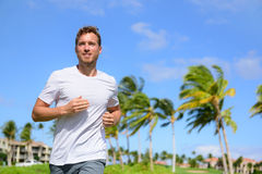 Healthy active man runner running in tropical park. Portrait of handsome young male jogger training cardio going for a run in city park or resort with palm Royalty Free Stock Image