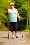 Senior woman practicing nordic walking in park Royalty Free Stock Photography