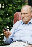 Healthy active senior 80+ with mobile phone. Active 83 year old male with mobile phone in garden Stock Photography