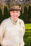 Healthy Active Senior Male. Healthy elderly man standing outside wearing an Irish fisherman's knit sweater and brown cap stock photos