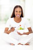 Healthy african american woman. Beautiful healthy african american woman eating green salad in bed Royalty Free Stock Photography