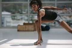 Healthy african woman working out in gym. Black sporty female exercising in fitness studio, looking at camera Royalty Free Stock Photography