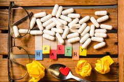 Healthy alphabet and capsule drug with glasses and red heart on wood  background Royalty Free Stock Photo