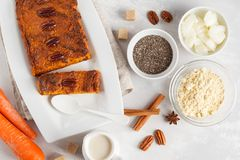 Healthy alternative vegan carrot cake, vegetarian pastries ingredients: chia, coconut butter, almond milk, nuts. Carrot bread, li. Ght background stock photography