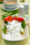 Healthy Appetizer For Dinner. Close-up healthy appetizer for dinner - fresh salad with tomatoes, greenery and yoghurt stock photos
