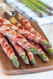 Healthy appetizer, green asparagus wrapped with bacon on wooden Stock Photography