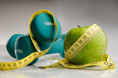 Healthy apple, measuring tape and dumbbells. For healthy living Stock Images
