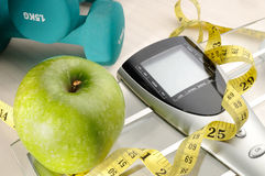 Healthy apple and sport. Apple, scale and dumbbells for a healthy life Royalty Free Stock Image