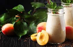 Healthy apricot smoothies with fresh fruits and flax seeds, in glass bottles, rustic kitchen table background, copy space,. Selective focus stock photos
