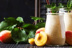 Healthy apricot smoothies with fresh fruits and flax seeds, in glass bottles, rustic kitchen table background, copy space,. Selective focus royalty free stock images