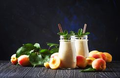 Healthy apricot smoothies with fresh fruits and flax seeds, in glass bottles, rustic kitchen table background, copy space,. Selective stock image