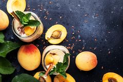 Healthy apricot smoothies in glass bottles and fresh fruits, top. View food still life royalty free stock image