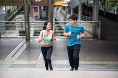 Healthy Asian couple running in city. Healthy Asian couple running upstairs at modern city skywalk. Active lifestyle sport people exercising cardio climbing Stock Photos