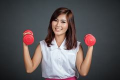 Healthy Asian girl hold  dumbbells with both hand Stock Photo