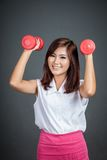 Healthy Asian girl hold  dumbbells and smile Stock Image