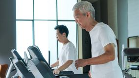Healthy Asian senior couple exercise together in gym running treadmill. Old healthy Asian senior couple exercise together in gym running treadmill royalty free stock images