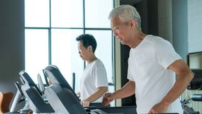 Healthy Asian senior couple exercise together in gym running treadmill. Old healthy Asian senior couple exercise together in gym running treadmill royalty free stock photo