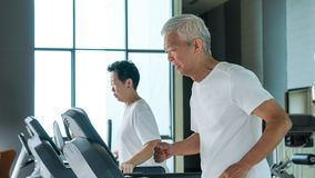 Healthy Asian senior couple exercise together in gym running treadmill. Old healthy Asian senior couple exercise together in gym running treadmill royalty free stock image