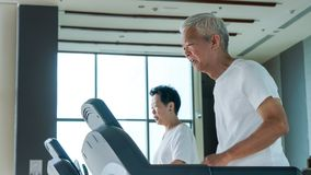 Healthy Asian senior couple exercise together in gym running treadmill. Old healthy Asian senior couple exercise together in gym running treadmill stock image