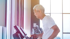 Healthy Asian senior couple exercise together in gym running treadmill. Old healthy Asian senior couple exercise together in gym running treadmill stock photos