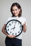 Healthy Asian woman drinking  glass of milk hold clock. Stock Images