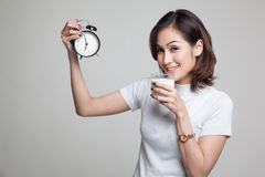 Healthy Asian woman drinking  glass of milk hold clock. Royalty Free Stock Images