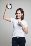 Healthy Asian woman drinking  glass of milk hold clock. Stock Photography
