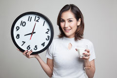 Healthy Asian woman drinking  glass of milk hold clock. Royalty Free Stock Image