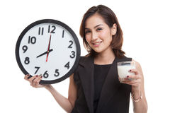 Healthy Asian woman drinking  glass of milk hold clock. Royalty Free Stock Photos