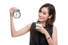 Healthy Asian woman drinking  glass of milk hold clock. Stock Photos