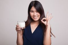 Healthy Asian woman drinking a glass of milk show OK sign. Royalty Free Stock Photo