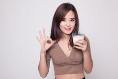 Healthy Asian woman drinking a glass of milk show OK sign. Royalty Free Stock Photos
