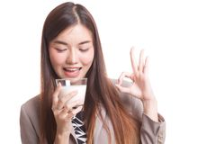 Healthy Asian woman drinking a glass of milk show OK sign. Royalty Free Stock Images
