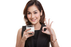 Healthy Asian woman drinking a glass of milk show OK sign. Royalty Free Stock Photography