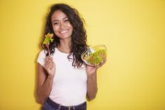 Healthy asian woman eating a bowl of salad. Portrait of healthy asian woman eating a bowl of salad on yellow background Stock Photo
