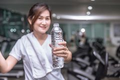 Healthy asian woman hand hold show bottle of drink water with sport club stock images